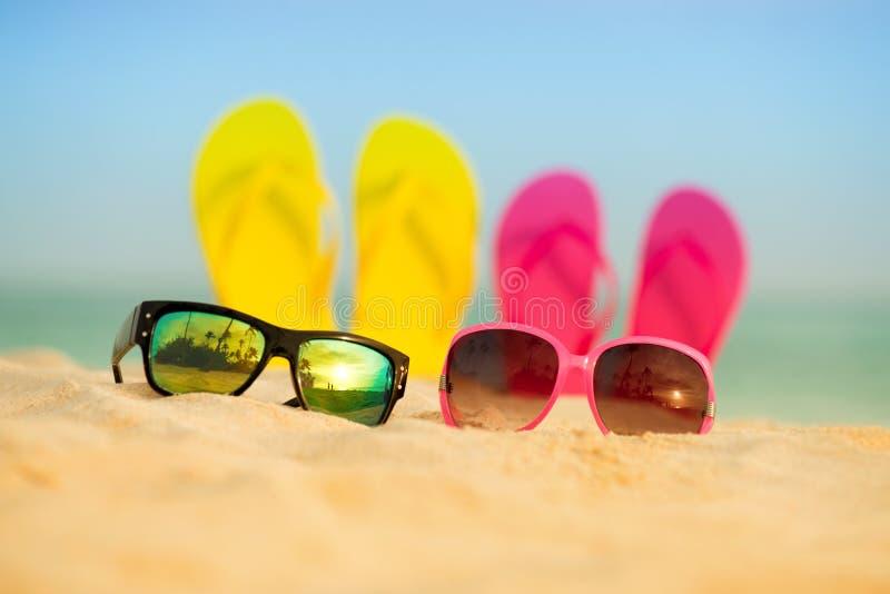 与黄色和桃红色凉鞋的玻璃在沙子站立以海为背景 免版税库存照片