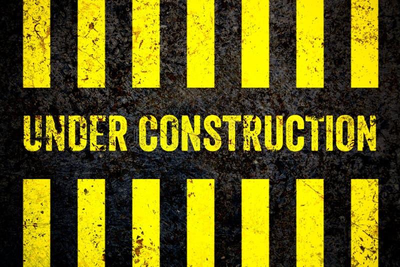与黄色和黑条纹的建设中警报信号被绘在破裂的混凝土墙粗糙的纹理背景 皇族释放例证