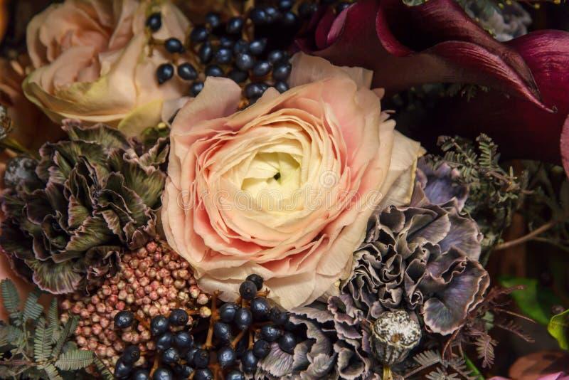 与黄色奶油玫瑰色特写镜头的黑暗的婚礼花束 库存照片