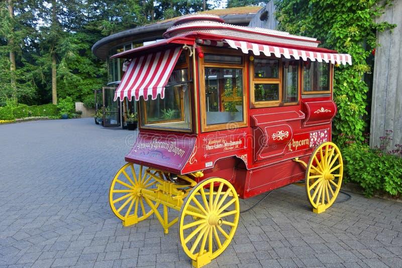 与黄色木轮子的古色古香的红色玉米花无盖货车恢复模型 免版税库存照片
