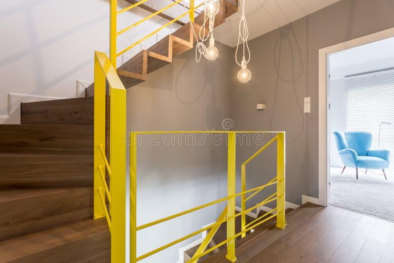 与黄色栏杆的木楼梯 免版税库存照片