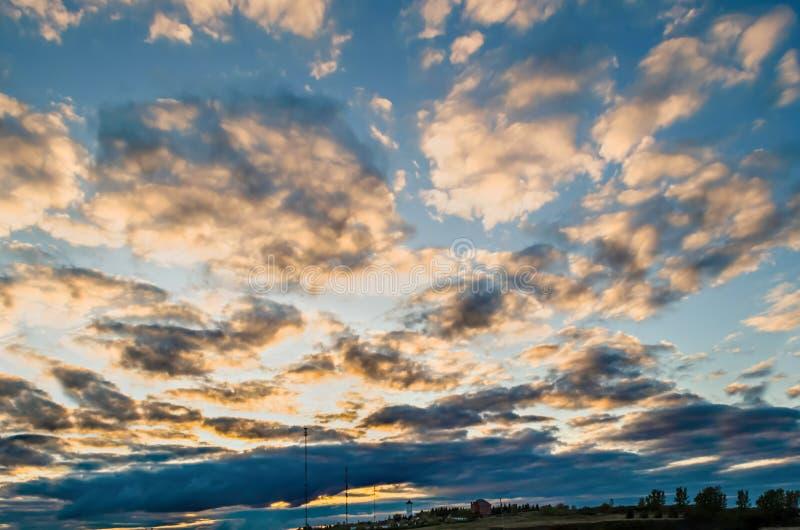 与黄色桃红色蓬松云彩、一个白色塔和一个大厦的巨大的不尽的天空在背景中 库存照片