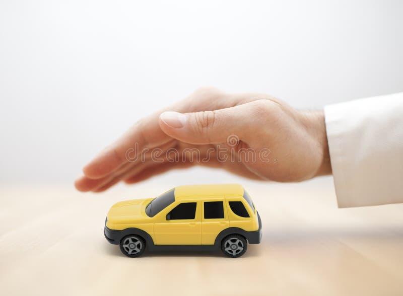 与黄色汽车玩具的汽车保险概念用手包括 图库摄影