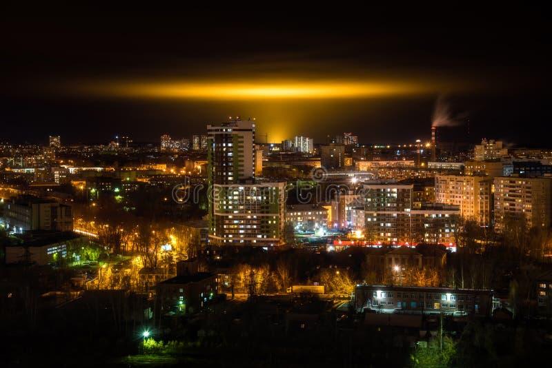 与黄色焕发的夜都市风景从工业温室的焕发天空的 免版税库存照片