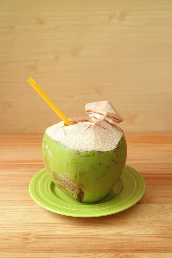 与黄色秸杆的新鲜的年轻椰子在一块绿色板材准备好喝 免版税库存照片
