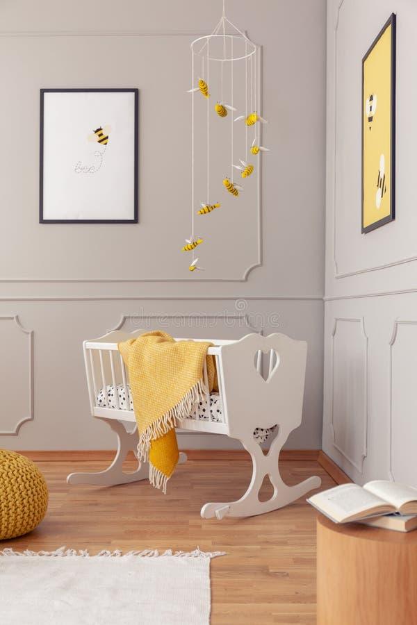 与黄色舒适毯子的白色木摇篮在时兴的托儿所中间 库存图片