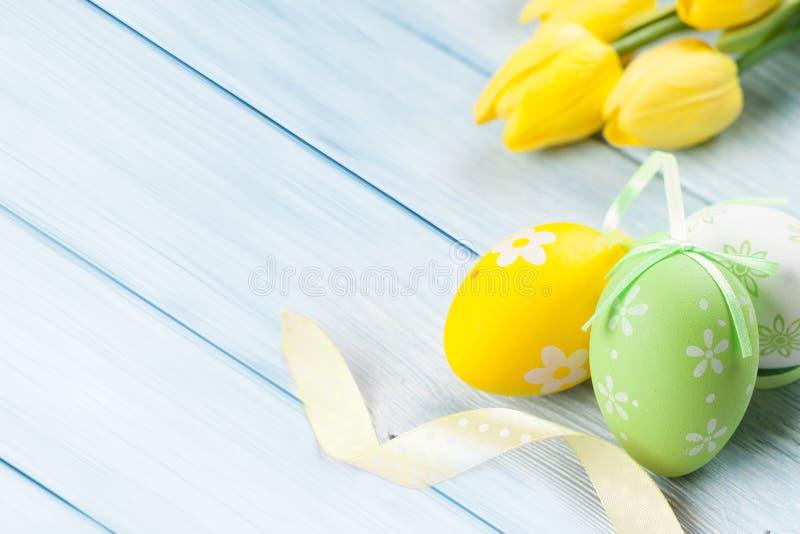 与黄色花的绿色色的复活节彩蛋在蓝色木baclgrund 免版税库存图片