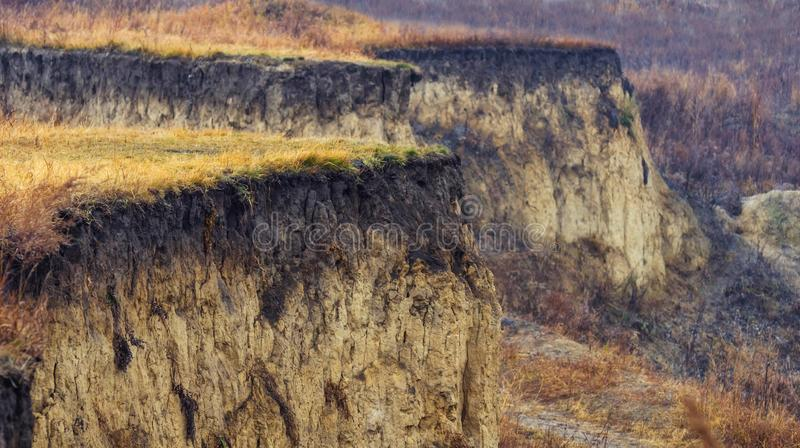 与黄色草的被风化的峡谷外缘在一晚秋天天 免版税库存照片