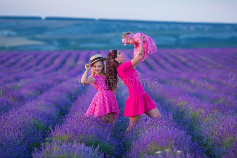 与黄色蒲公英花一起的愉快的母亲和女儿孩子在夏日一起享受愉快假期的时间 免版税库存照片