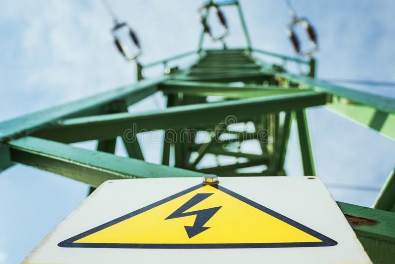 与黄色警告的绿色电帆柱力量塔和小心签署在背景的高压和蓝天 电定向塔 库存照片