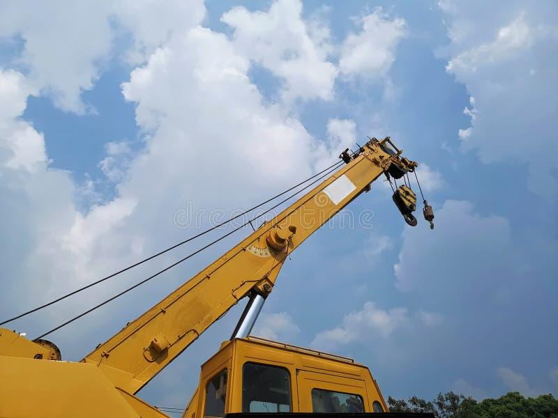 与黄色起重机卷扬机的望远镜景气在工地工作的反对多云天空 库存图片