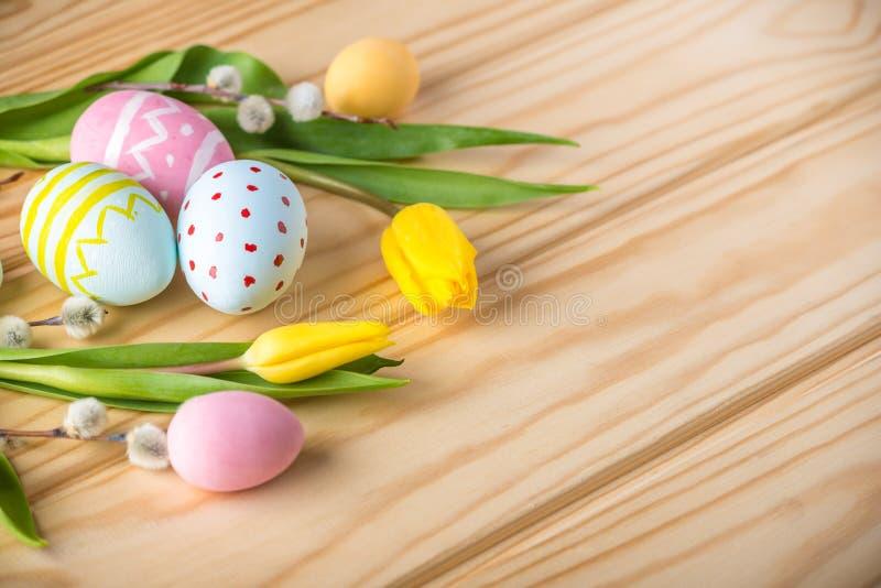 与黄色郁金香的五颜六色的复活节彩蛋手画在轻的木背景 欢乐春天卡片 免版税库存图片