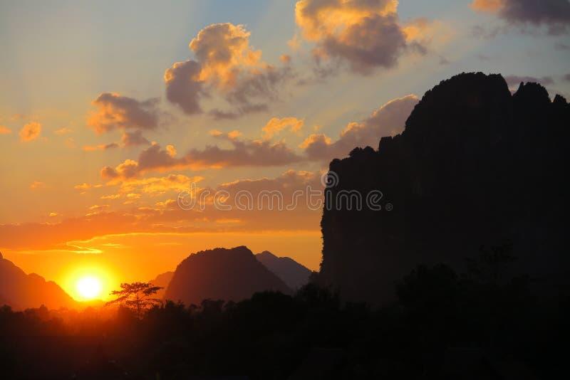 与黄色金黄颜色和石灰岩地区常见的地形石灰石山脉- Vang Vieng,老挝黑剪影的日落  免版税库存照片
