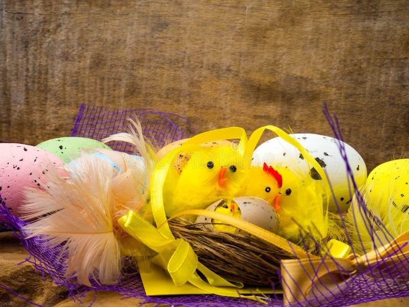 与黄色鸡的复活节装饰构成筑巢,颜色鸡蛋和五颜六色的羽毛在木板 免版税库存照片