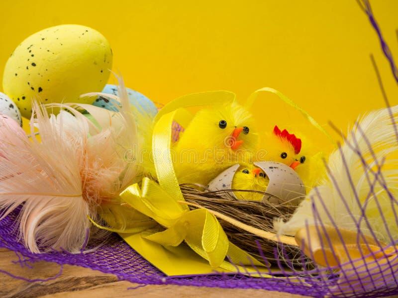 与黄色鸡的复活节装饰构成筑巢,颜色鸡蛋和五颜六色的羽毛在木板 库存照片