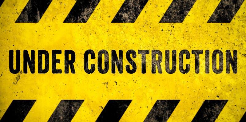 与黄色黑条纹的建设中警报信号文本被绘在混凝土墙水泥门面纹理背景横幅 向量例证