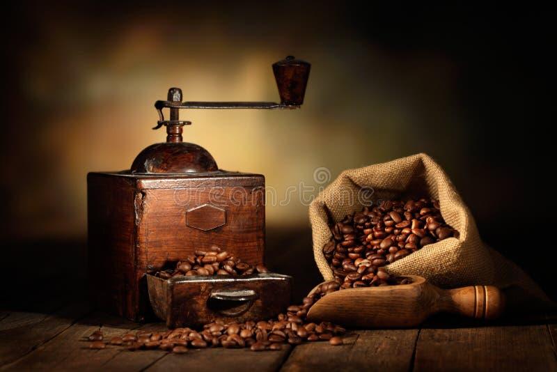 与黄麻袋子和咖啡豆的老研磨机 库存图片