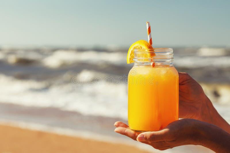 与黏浆状物质的橙汁在海滩的手上 免版税库存照片