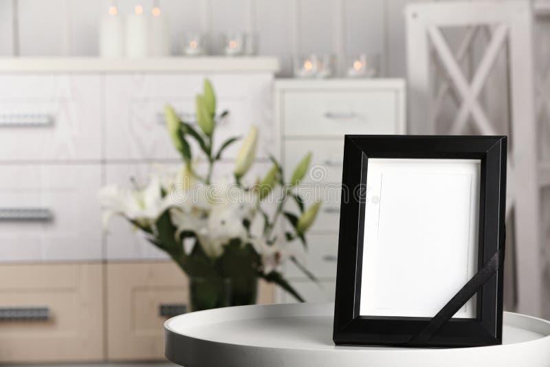与黑丝带的葬礼照片框架在tabl 免版税库存照片