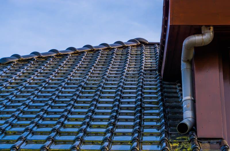 与黑光滑的屋顶盖瓦和排水管,现代荷兰建筑学背景的屋顶 库存图片
