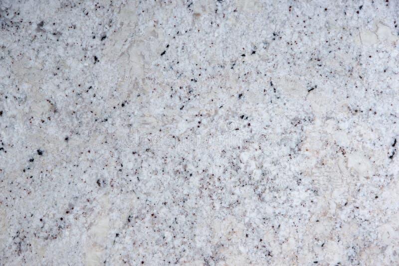 与黑小点的背景自然白色石头,称花岗岩意想不到的白色 免版税库存图片