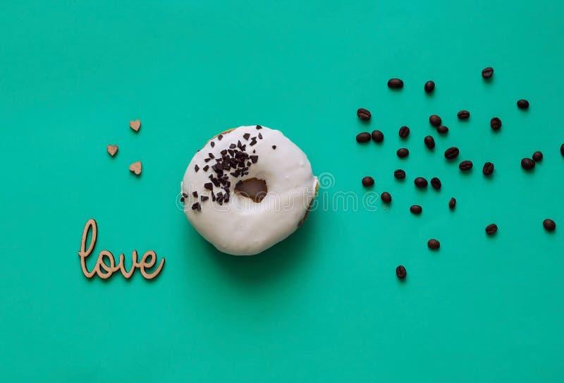 与黑巧克力甜点的白色上釉圆环 平的位置 食物创造性的概念 在薄荷的背景的绿色霓虹心情 免版税库存图片