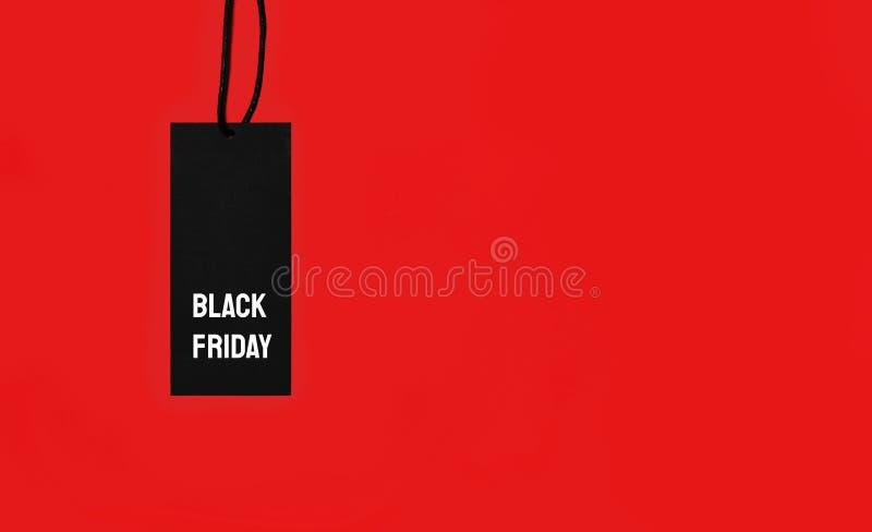 与黑星期五题字的销售标记在红色背景 库存图片