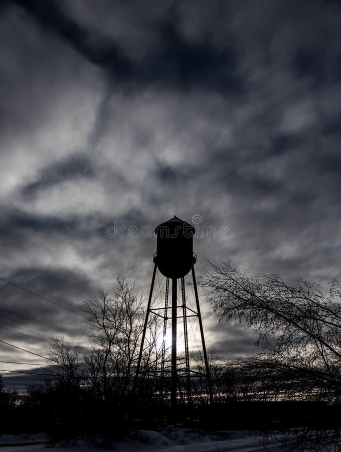 与黑暗的天空的水塔剪影 免版税图库摄影