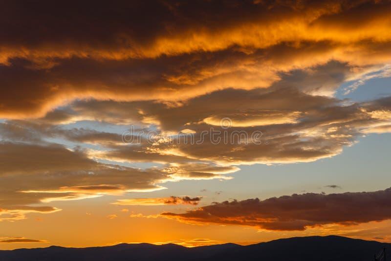 与黑暗的重的云彩的日落,美好的风景 库存图片