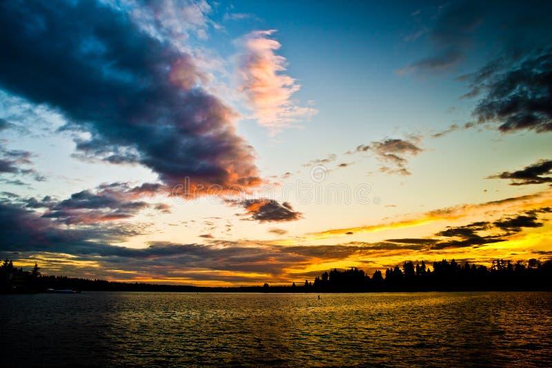 与黑暗的金黄日落互换在Meydenbauer海滩公园, Bellevue,华盛顿,美国 免版税库存照片