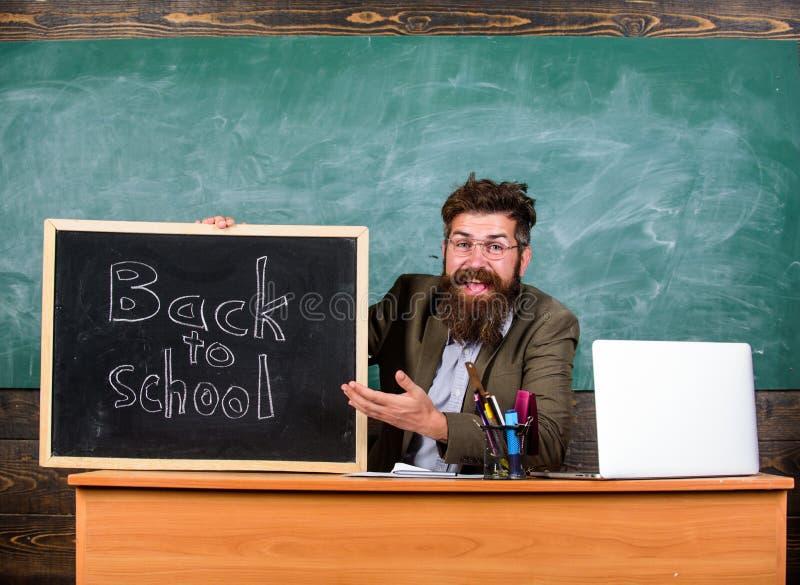 与黑板题字的老师或校长欢迎回到学校 开始新的学期  库存图片