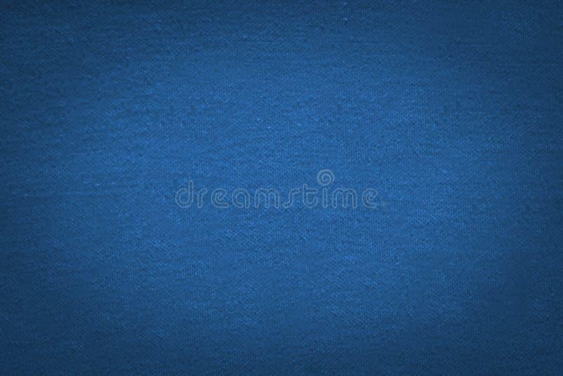 与黑梯度小插图的蓝色布料纹理背景 库存图片