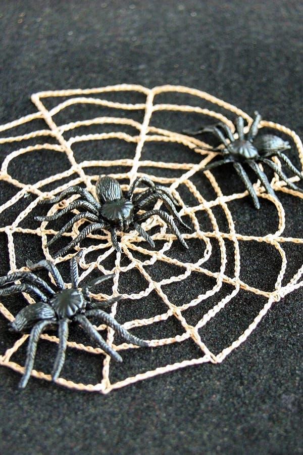 与黑橡胶蜘蛛的钩针编织的蜘蛛网在黑天鹅绒背景 黑暗的万圣夜10月概念 免版税库存照片