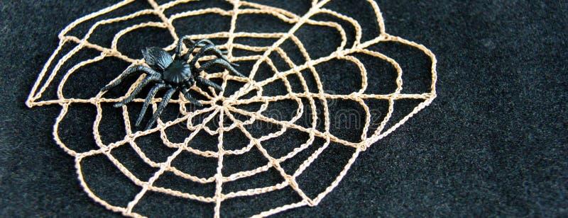 与黑橡胶蜘蛛的钩针编织的蜘蛛网在黑天鹅绒背景 黑暗的万圣夜10月概念 免版税库存图片