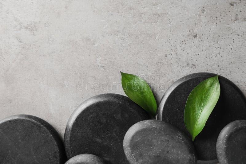 与黑温泉石头和绿色叶子的平的被放置的构成在颜色背景 库存图片