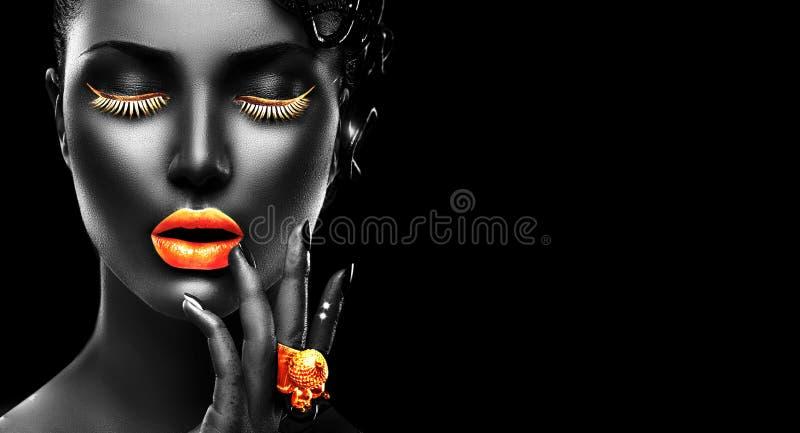 与黑皮肤、金黄嘴唇、睫毛和首饰-金黄圆环的时装模特儿在手边 在黑色背景 免版税库存照片