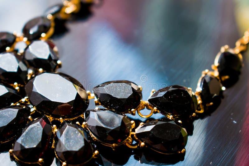 与黑石头的典雅的项链和一金黄金属基反射性黑镜子表面上 黑暗的宝石以形式 库存图片