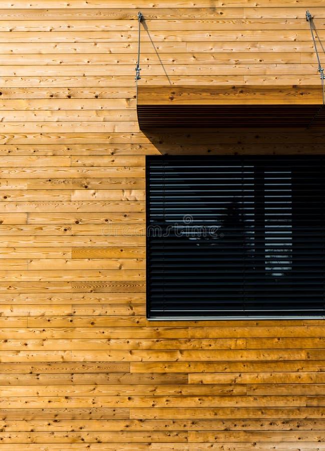 与黑窗口现代建筑学的木大厦 免版税库存照片