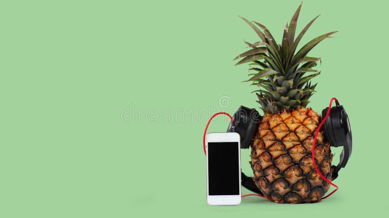 与黑耳机和智能手机的新鲜的菠萝有反对绿色背景的黑屏幕的 库存照片