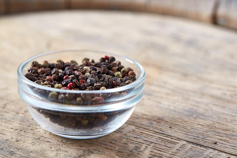 与黑胡椒种子的静物画在木桶,特写镜头,浅景深的玻璃瓶子 免版税库存照片