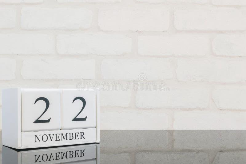 与黑色11月22日词的特写镜头白色木日历在黑玻璃桌和白色砖墙上构造了与拷贝的背景 库存照片