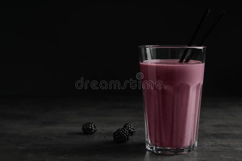 与黑莓酸奶圆滑的人的玻璃在灰色桌上 库存图片
