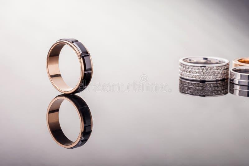 与黑陶瓷的一个金子定婚戒指和一个光滑的表面和对上的反射圆环在背景中 库存照片