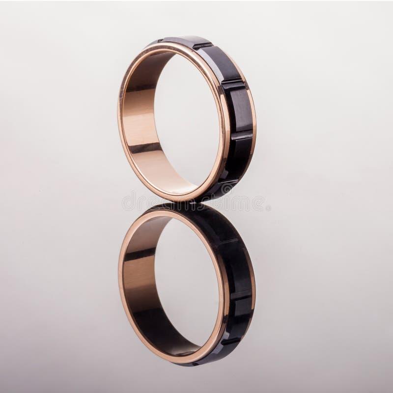 与黑陶瓷的一个金子定婚戒指和光滑的表面上的反射 免版税库存图片