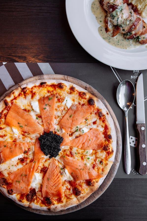 与黑鱼子酱关闭的熏制鲑鱼意大利比萨顶视图 免版税图库摄影