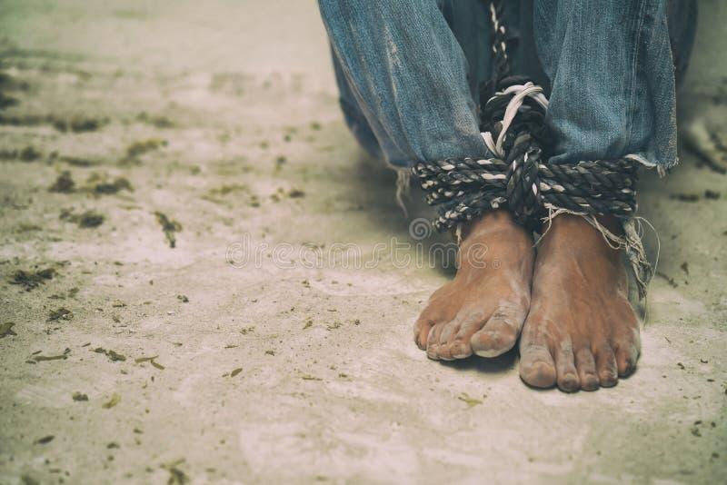 与绳索一起被栓的绝望的人脚 免版税库存照片