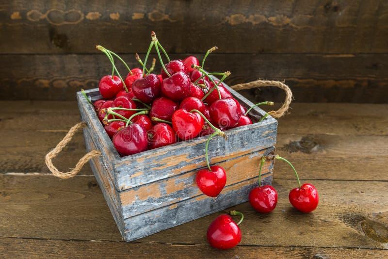 与水下落的樱桃在葡萄酒木箱 免版税图库摄影