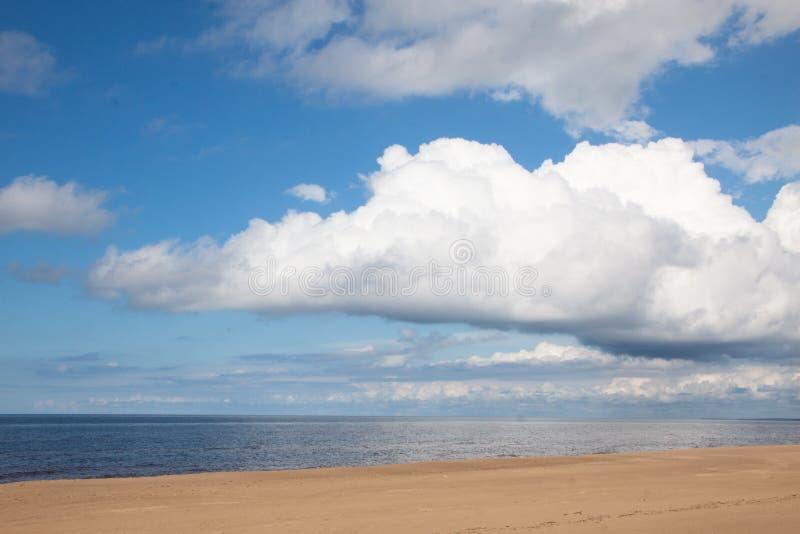 与令人惊讶的云彩的海边 免版税库存图片