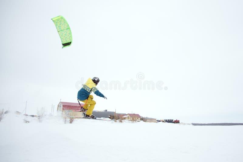 与年轻人的极端自由式跳高滑雪冬天季节的 snowkiting 库存图片