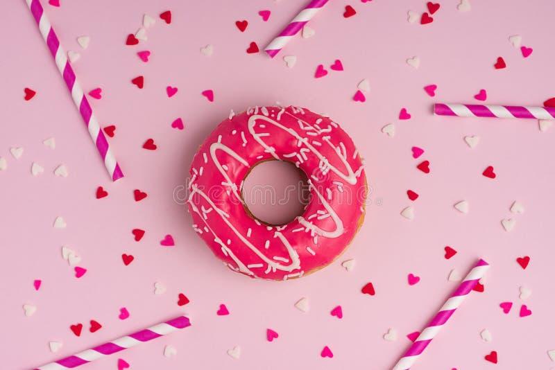 与结冰的油炸圈饼在与copyspace的粉红彩笔背景 Swee 免版税库存照片